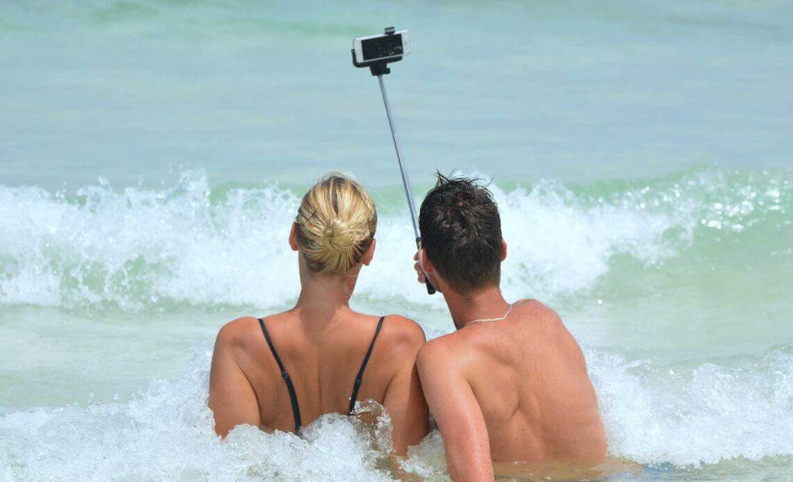 Narcissistic man and woman taking selfie on beach