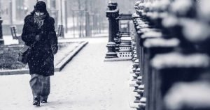 resilience to the cold - woman walking in the city snow