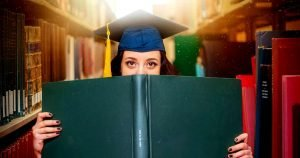 high IQ teens are liked more by their peers - hig school graduate holding diploma