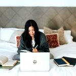 working from home - woman with laptop on bed