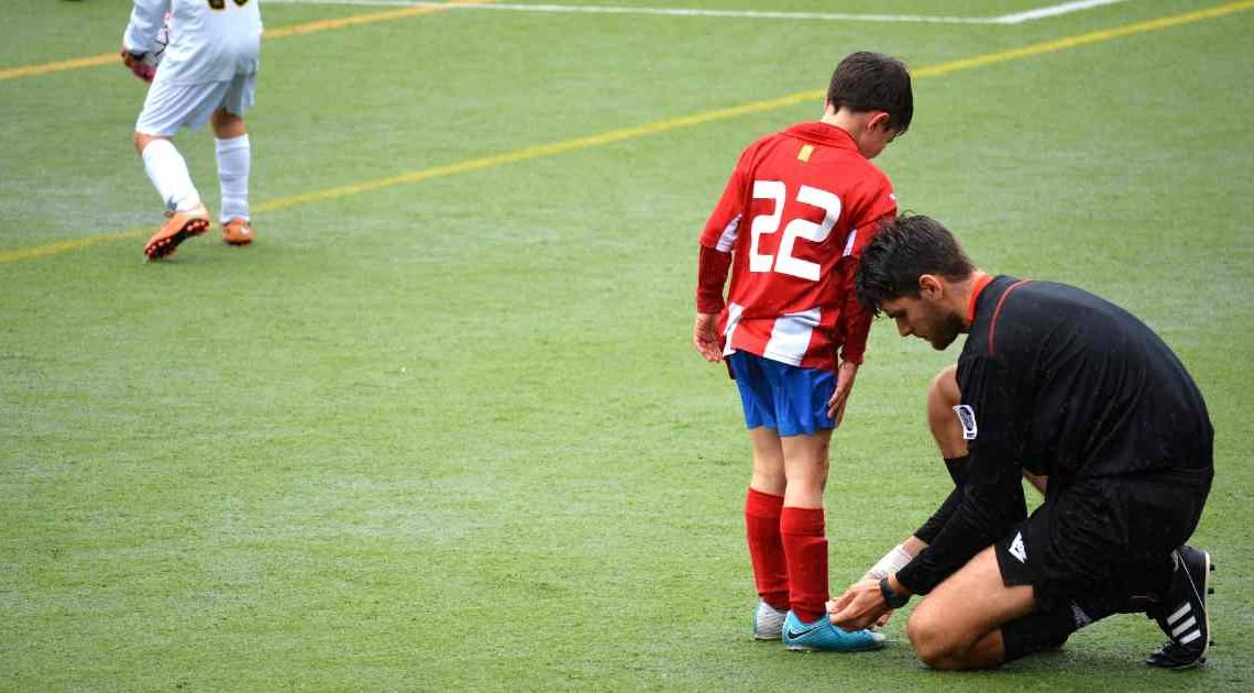 agreeableness measured by fMRI - man helps young soccer player tie his shoe