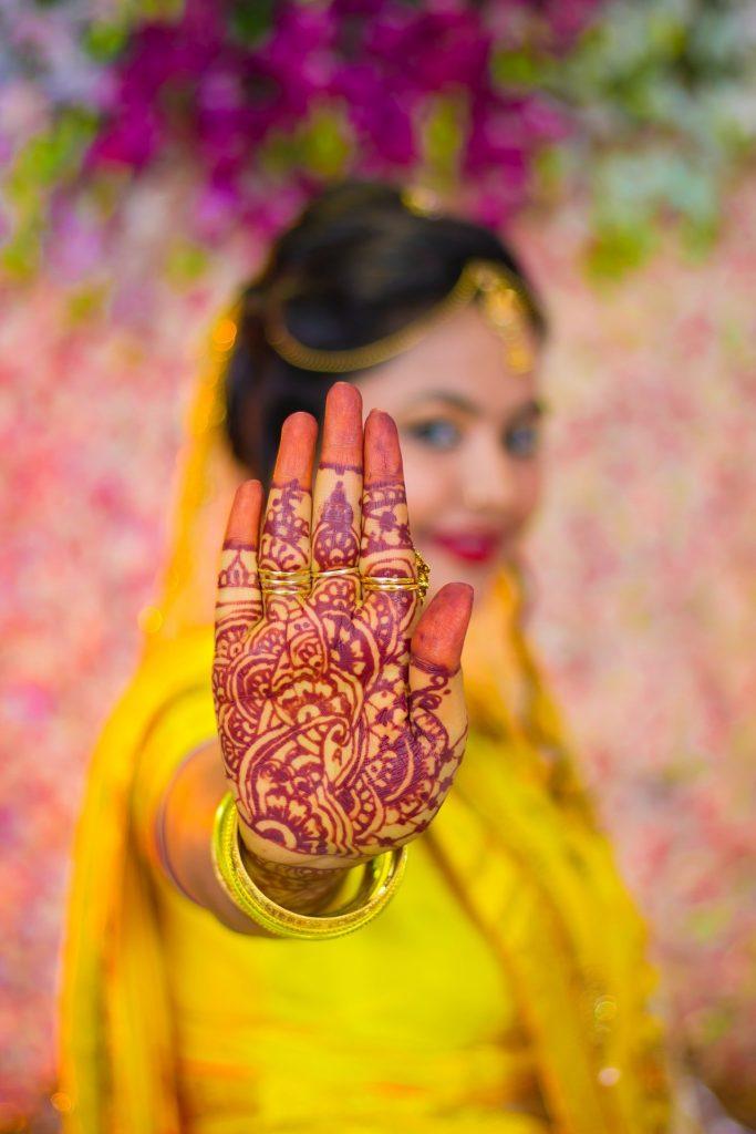 amazing red-orange mehndi design on the palm